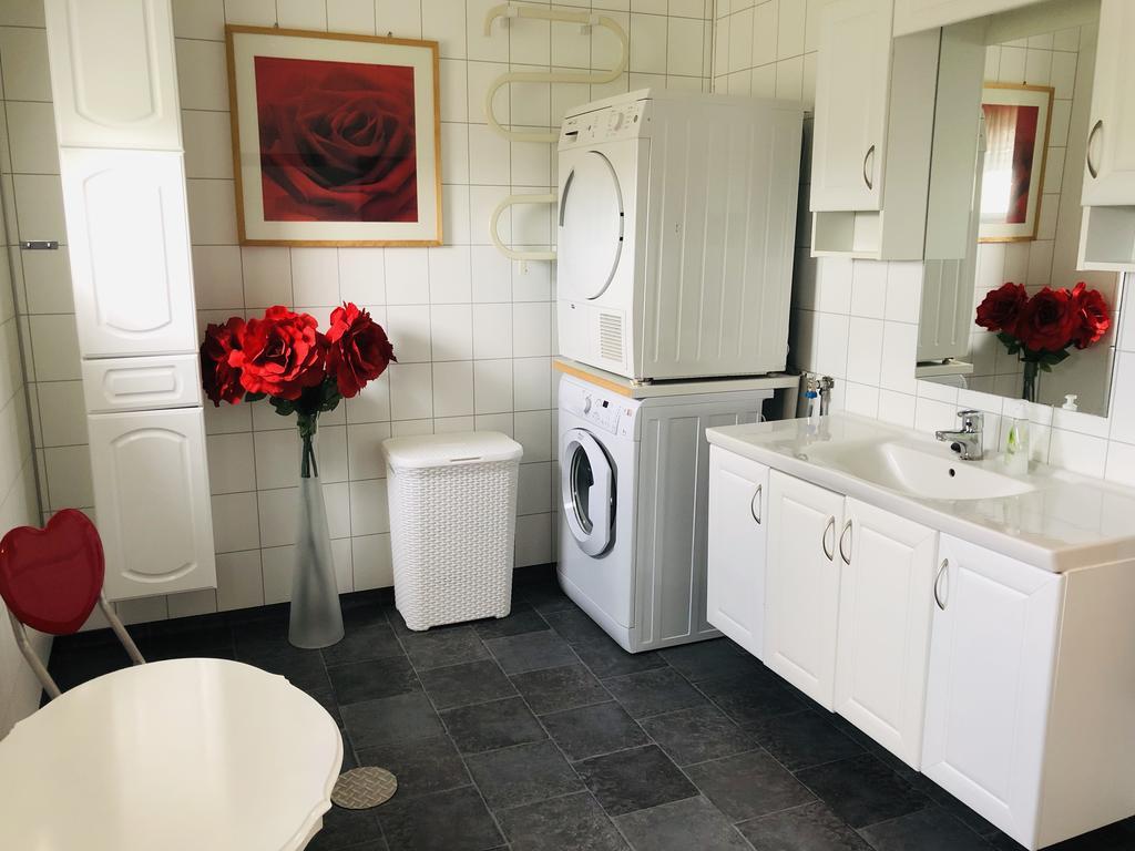 Bad med vaskemaskin, vask, speil, og skap