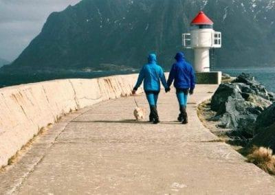 To personer går tur med hund til fyrtårn