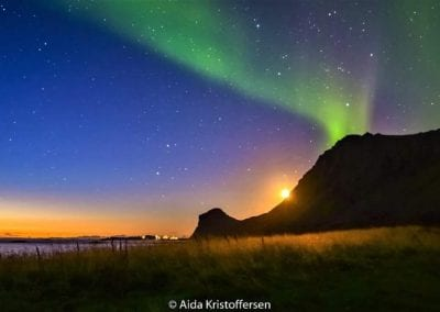 Northern lights and the sun behind a mountain