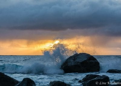 Waves strikes against rock during a sunset