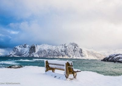 Snow-filled bench and hill with a large mountain and sea in the background