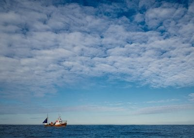 Fishing boat at sea with a blue sky