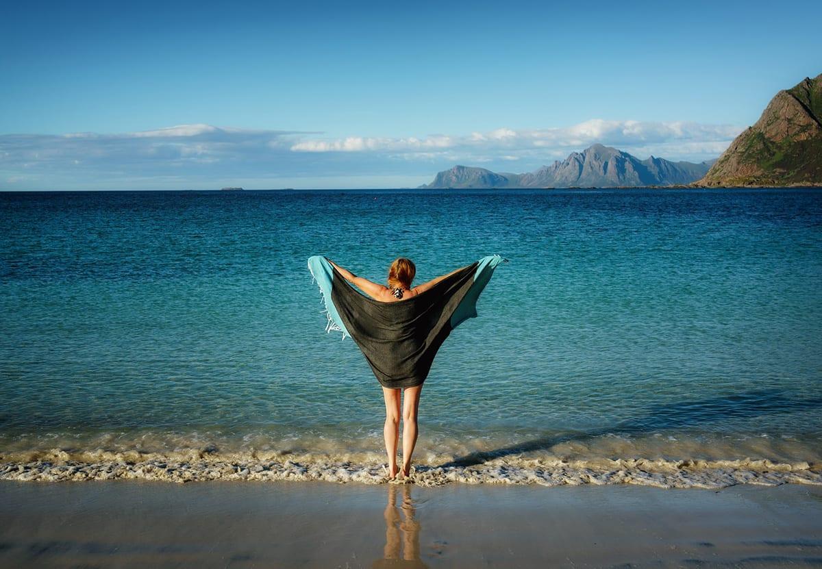 Person som står på en strand nær havet
