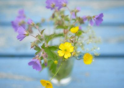 Purple and yellow flowers in a glass