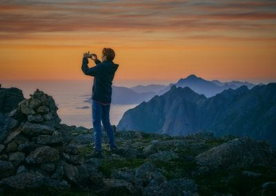 A person up on a mountain takes a picture of the sunset with a telephone