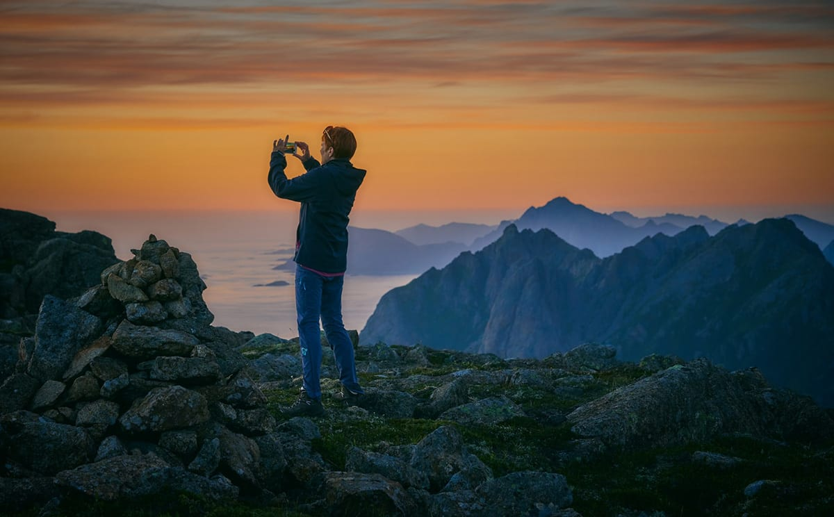 Person oppe på ett fjell tar bilde av solnedgangen med telefon